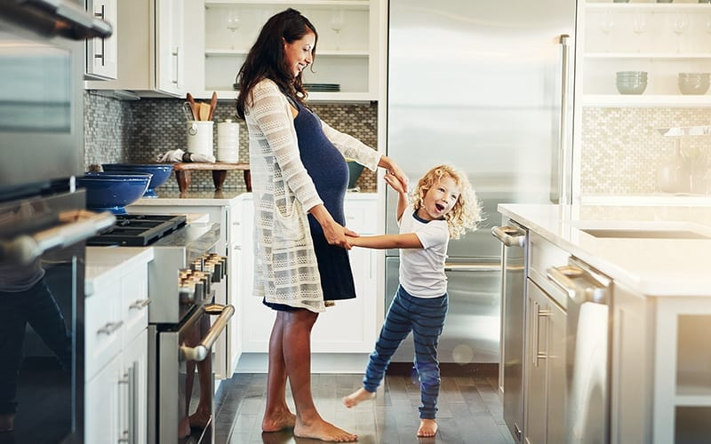 pregnant mom dancing with daughter in kitchen