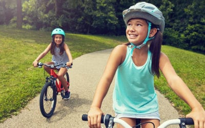 photo of kids with helmets on bikes